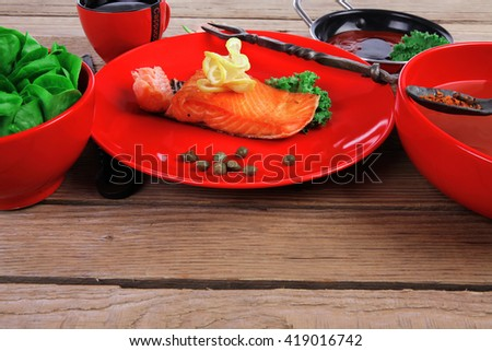 delicious portion of fresh roast salmon fillet on red plate with green salad kale tomato soup bbq sauce and black coffee over wooden table - healthy food, diet cooking concept  - stock photo