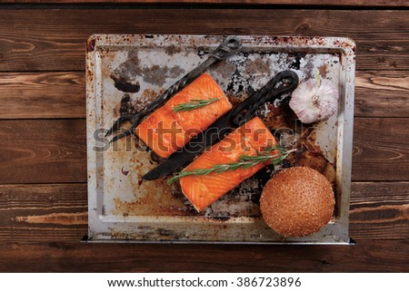 delicious portion of raw fresh salmon fillet with aromatic herbs and spices on vintage tray over wooden table - healthy food, diet cooking concept with background space - stock photo