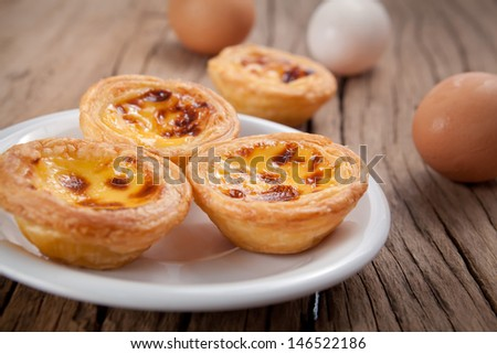 delicious portuguese egg tart on wood background - stock photo