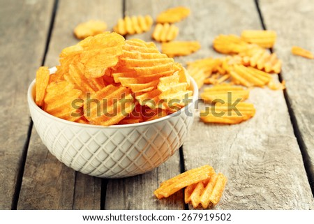 Delicious potato chips in bowl on wooden table close-up - stock photo