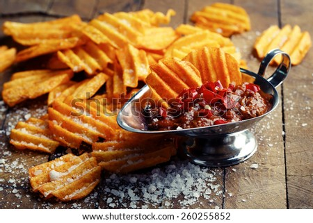 Delicious potato chips with sauce on wooden table close-up - stock photo