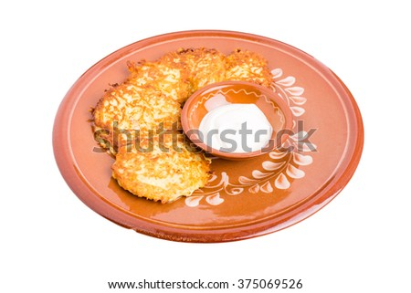 Delicious potato pancakes on brown clay plate with sour cream. Isolated on a white background. - stock photo