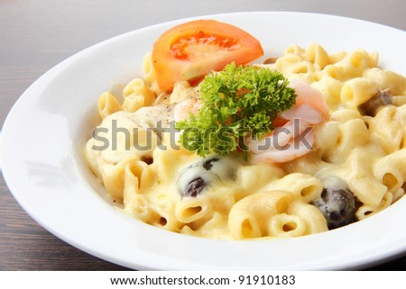 Delicious prawn macaroni pasta with cheese and mushrooms on a white plate together with the fork & spoon on wooden table - stock photo