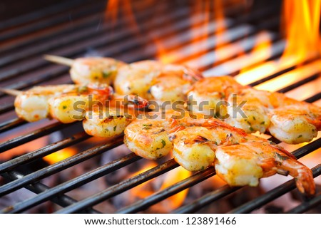 delicious prawn spit on grill with flames in background - stock photo