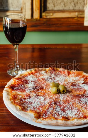Delicious Prosciutto Pizza and Glass of Wine on wooden table in a rustic restaurant. Ingredients peeled tomato, cheese, ham, fresh tomato, parmesan, olives. - stock photo