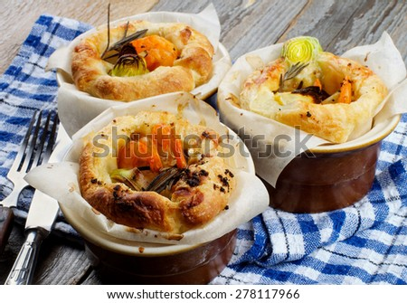 Delicious Puff Pastry Snacks with Shrimps, Leek and Cheese Oven-Baked in Ramekin with Fork, Knife and Napkin closeup on Wooden background - stock photo