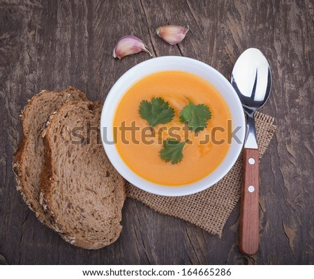 Delicious pumpkin soup and bread flour. On the decorative vintage table. - stock photo