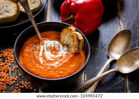 Delicious pumpkin soup with heavy cream on dark rustic wooden table with red bell pepper, bread toasts, lentil, tomatoes  - stock photo