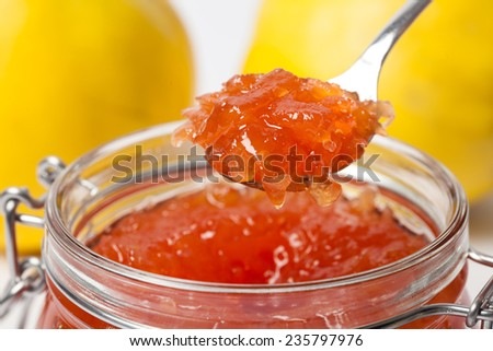 Delicious quince jam in a spoon on a ripe quinces background. - stock photo
