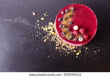 Delicious raspberry cake with fresh strawberries, raspberries, blueberry, currants and pistachios on black background. Free space for your text. - stock photo