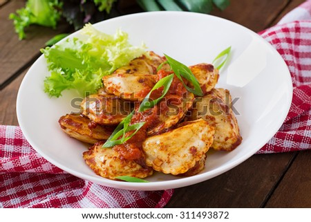 Delicious ravioli with tomato sauce and green onions - stock photo