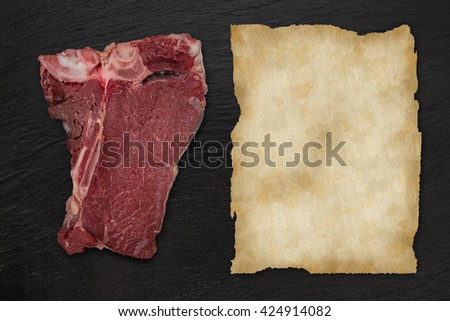 Delicious raw T-bone beef steak on black stone table, close-up. - stock photo
