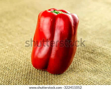 Delicious red capsicum on hessian background - stock photo