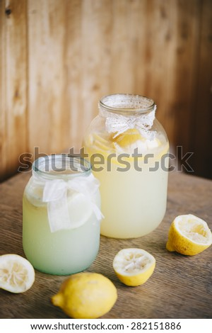 Delicious refreshing ice cold lemonade in glass two jars on the wooden table