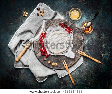 Delicious ripe camembert cheese on wooden cutting board with berries and sauce on rustic background, top view. Traditional milk dairy product  - stock photo