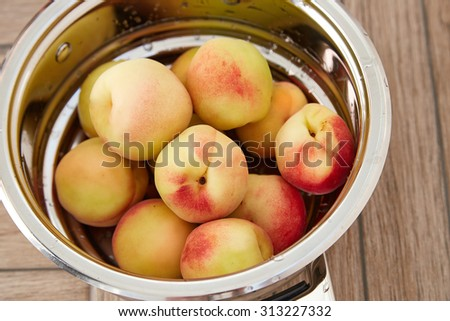 Delicious ripe delicious juicy ruddy peaches or apricots lying in a tin bowl, vitamins, organic food diet summer fruits ripen in the sun and heat - stock photo