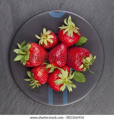 Delicious ripe strawberries on black plate on black stone, flat lay. Healthy fruit eating. - stock photo