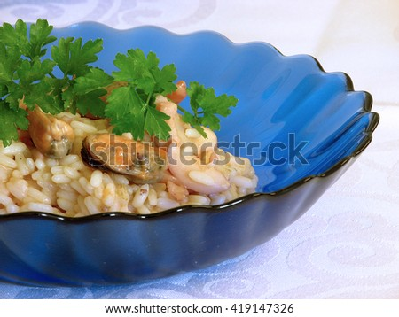 Delicious risotto with mixed seafood in a blue plate                                - stock photo