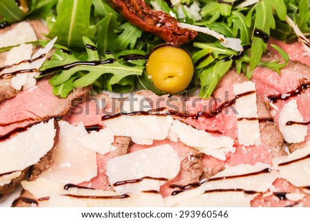 Delicious roast beef with arugula and parmesan covered with balsamic vinegar. Macro. Photo can be used as a whole background. - stock photo