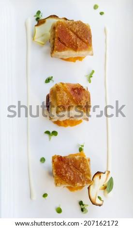 Delicious roasted pork belly cubes on baked pumpkin with fried apple chips and a cauliflower puree with oregano and sage. - stock photo