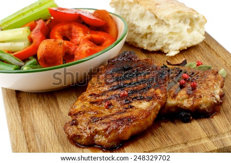 Delicious Roasted Pork Steaks with Vegetable Stocks and Flap of Bread on Wooden Cutting Board isolated on white background. Focus on Steaks - stock photo
