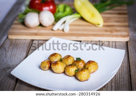 Delicious roasted potatoes on a plate with fresh vegetables - stock photo