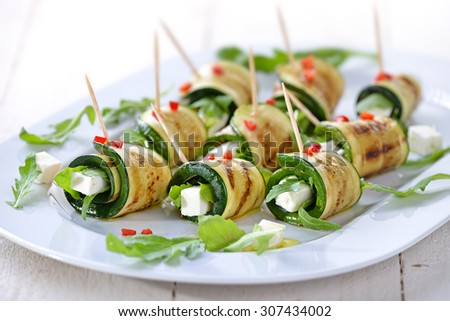 Delicious rolls of fried zucchini slices and feta cheese with rucola, served with olive oil and pieces of bell peppers - stock photo