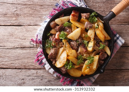 Delicious rustic fried potatoes with meat and bacon in a pan. horizontal top view - stock photo