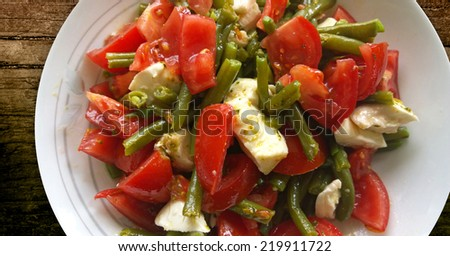 Delicious salad of sliced ripe tomatoes, green beans and mozzarella cheese with olive oil, balsamic vinegar and  basil dressing - stock photo