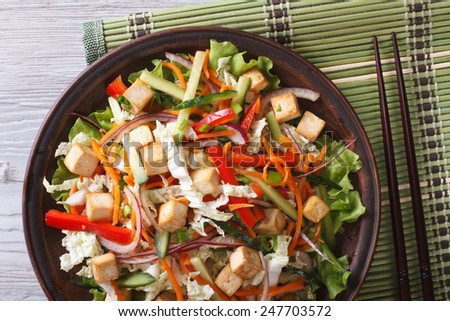 Delicious salad of tofu with fresh vegetables close-up on a plate. horizontal view from above  - stock photo