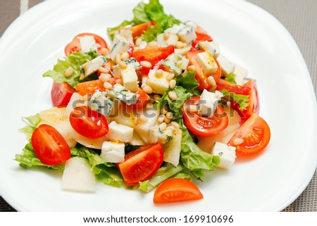 Delicious salad with gorgonzola, pear and cherry tomatoes close-up - stock photo