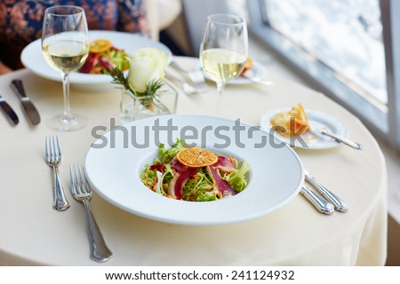 Delicious salad with herbs, smoked duck breast and dry orange - stock photo