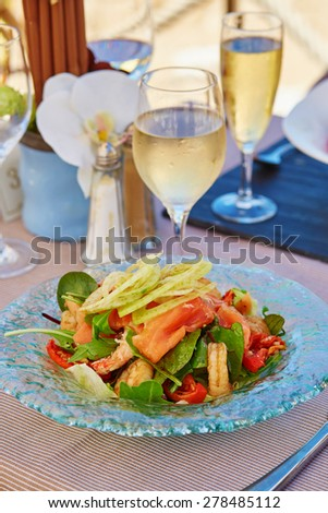 Delicious salad with smoked salmon and prawns served with glass of champagne in a beach restaurant - stock photo
