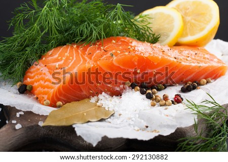 Delicious salmon fillet, rich in omega 3 oil, aromatic spices and lemon on fresh lettuce leaves on black background. Healthy food, diet and cooking background. - stock photo