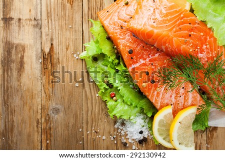 Delicious salmon fillet, rich in omega 3 oil, aromatic spices and lemon on fresh lettuce leaves on rustic wooden background. Healthy food concept. With copy space.  Top view. - stock photo