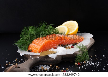 Delicious salmon fillet, rich in omega 3 oil, aromatic spices and lemon on vintage cutting board on black wooden background. Healthy food, diet and cooking concept. - stock photo