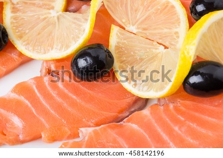 Delicious salmon fillet with lemons and olives. Macro. Photo can be used as a whole background. - stock photo