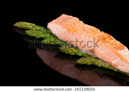 Delicious salmon steak isolated on black background. Culinary healthy seafood eating. - stock photo