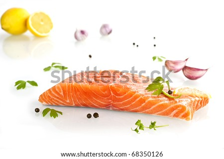 Delicious salmon steak with lemon, parsley and garlic isolated on white background. - stock photo