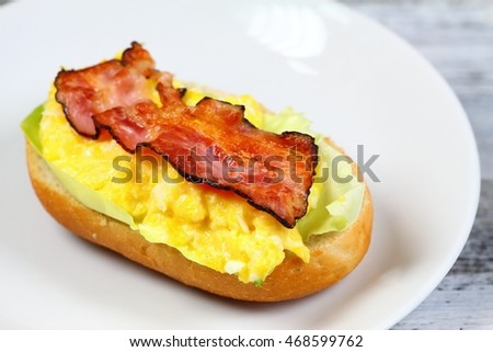Delicious sandwich with bacon, scrambled egg and lettuce served on a plate