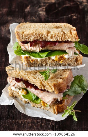 Delicious sandwich with meat, vegetables and mustard on a wooden background. - stock photo