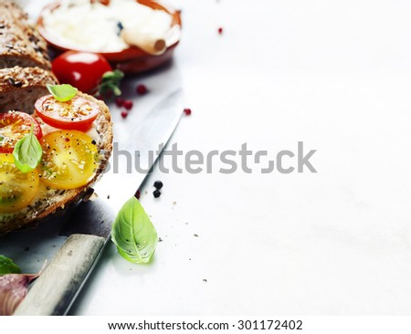 Delicious sandwich with slices of tomatoes and basil on white marble background - stock photo