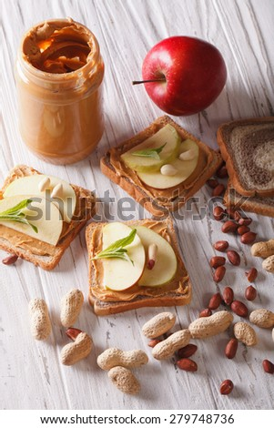 Delicious sandwiches with peanut butter and apple close-up on the table. vertical  - stock photo