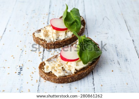 Delicious sandwiches with radish and basil on wooden background - stock photo