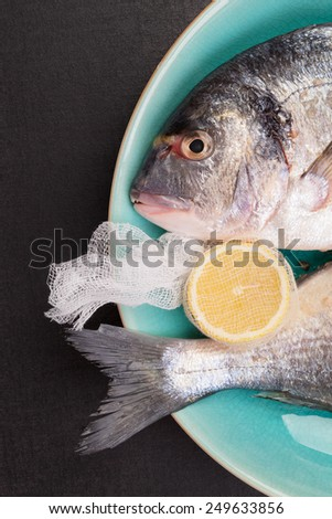 Delicious sea bream with lemon on turquoise plate on black background, top view. Mediterranean seafood background. - stock photo