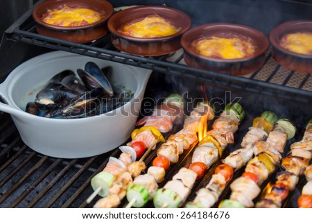 Delicious seafood outdoor meal at the BBQ with grilled salmon shish kebabs, marine mussels and individual pots of sausage stew, close up view on the grill - stock photo