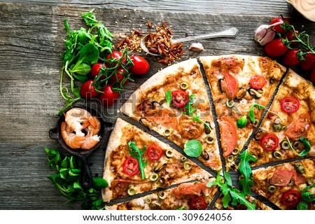 Delicious seafood pizza on a wooden textured table - stock photo