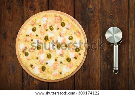 Delicious seafood pizza with salmon, capers and olives - thin pastry crust isolated at wooden background with stainless steel cutter, above view - stock photo