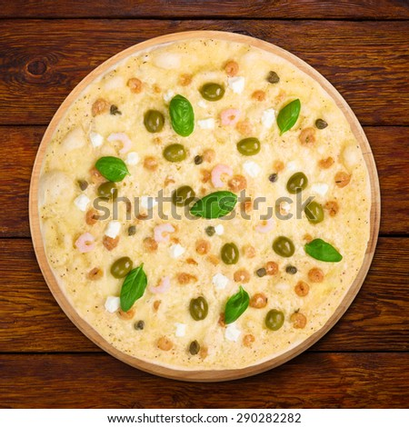 Delicious seafood pizza with shrimps, calamari rings, capers and olives - thin pastry crust at wooden table background, above view - stock photo