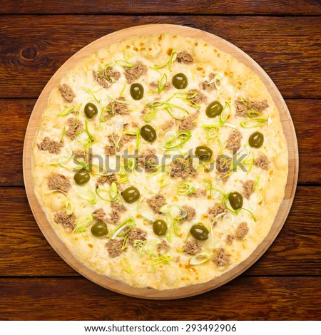 Delicious seafood pizza with tuna fish, olives and leek - thin pastry crust at wooden table background, above view  on wooden desk - stock photo